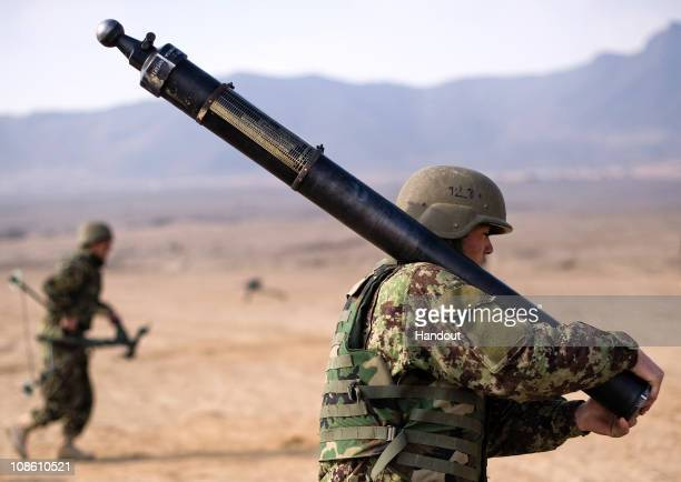 In this hand out image provided by NATO Training Mission Afghanistan soldiers assigned to an Afghan National Army weapons company carry parts of an...
