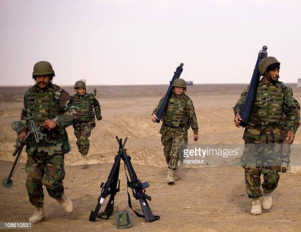 In this hand out image provided by NATO Training Mission - Afghanistan, soldiers assigned to an Afghan National Army weapons company carry parts of...