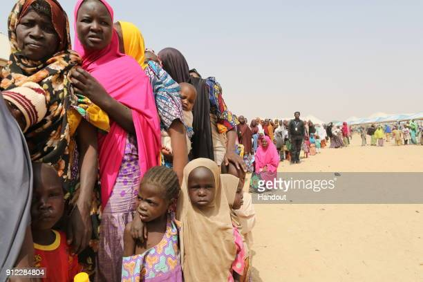 In this hand out supplied by International Medical Corps Families displaced by the Boko Haram insurgency line up for food being distributed by...