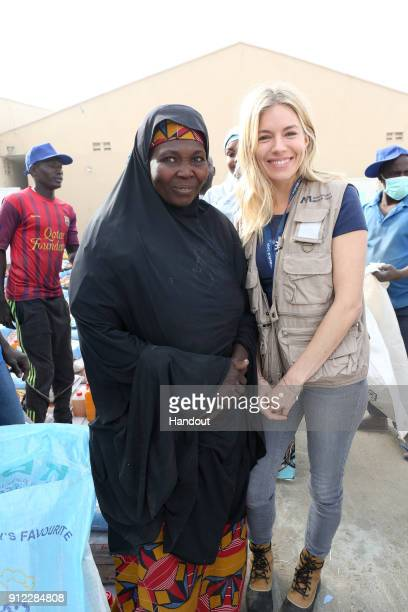 In this hand out supplied by International Medical Corps Sienna Miller International Medical Corps Global Ambassador meets with a woman displaced by...