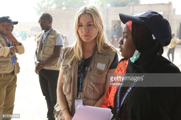 In this hand out supplied by International Medical Corps Sienna Miller International Medical Corps Global Ambassador visits with survivors of the...