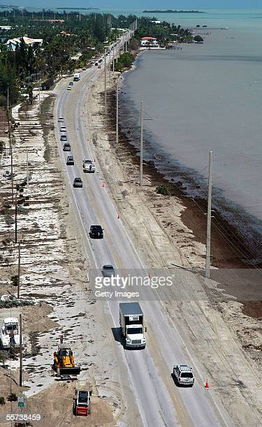 In this handount photo provided by the Florida Keys News Bureau frontend loaders work to clear sand and seaweed from the Overseas Highway a day after...