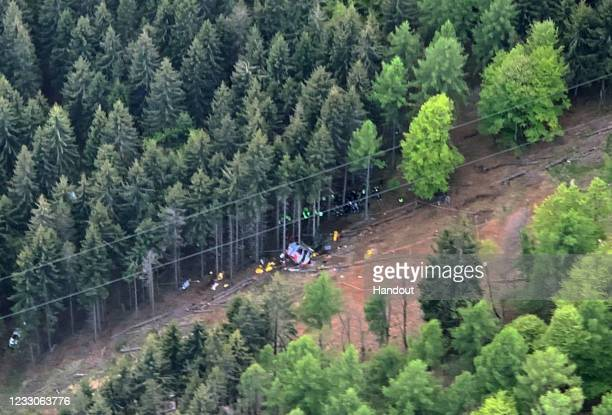 In this handout aerial photo provided by the Carabinieri, emergency workers surround the wreckage of a cable car that fell from the...