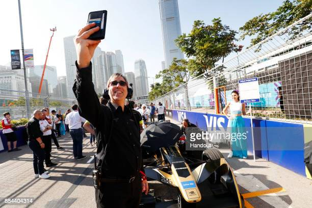 In this handout from FIA Formula E Mark Preston takes a selfie with the car of Jean Eric Vergne TECHEETAH Renault ZE 17 during the Hong Kong ePrix...