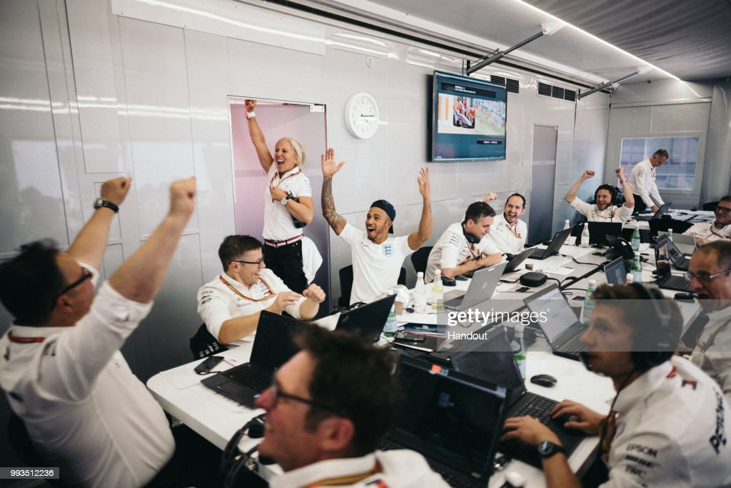 In this handout from Mercedes GP - Lewis Hamilton (c) of Great Britain and Mercedes GP celebrates with team mates in their engineering room in the F1 paddock as England score against Sweden in their World Cup 2012 Russia quarter final match in Samara, at Silverstone on July 7, 2018 in Northampton, England.