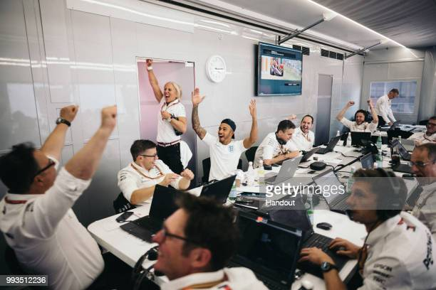 In this handout from Mercedes GP Lewis Hamilton of Great Britain and Mercedes GP celebrates with team mates in their engineering room in the F1...