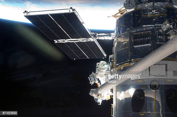 In this handout from NASA Astronaut Andrew Feustel perched alone on the end of the Space Shuttle Atlantis' remote manipulator system arm participates...