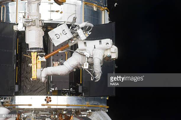 In this handout from NASA Astronaut Andrew Feustel STS125 mission specialist positioned on a foot restraint on the end of Atlantis' remote...