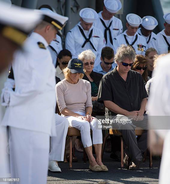 In this handout from NASA Carol Armstrong wife Eric Rick Armstrong son of Neil Armstrong and other family members bow their heads during Neil...