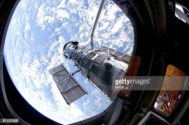 In this handout from NASA the Hubble Space Telescope is grappled to Space Shuttle Atlantis STS125 by the shuttle's Canadianbuilt remote manipulator...
