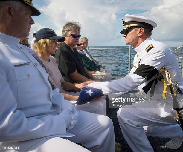 In this handout from NASA US Navy Captain Steve Shinego commanding officer of the USS Philippine Sea presents the US flag to Carol Armstrong...