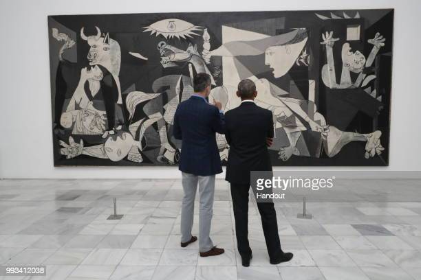 """In this handout from the Casa Real - King Felipe VI of Spain and former President Barack Obama view Picasso's """"Guernica"""" as they visit Reina Sofia..."""
