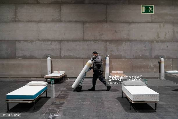 In this handout from the Comunidad de Madrid, workers install a field hospital for coronavirus patients in Ifema on March 21, 2020 in Madrid, Spain....