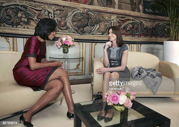 In this handout from the French presidency press services US first lady Michelle Obama speaks with France's first lady Carla BruniSarkozy before a...