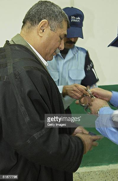 In this handout from the Iraqi Special Tribunal Sultan Hashem Saddam Hussein's former defense minister is escorted by Iraqi Police durign a hearing...