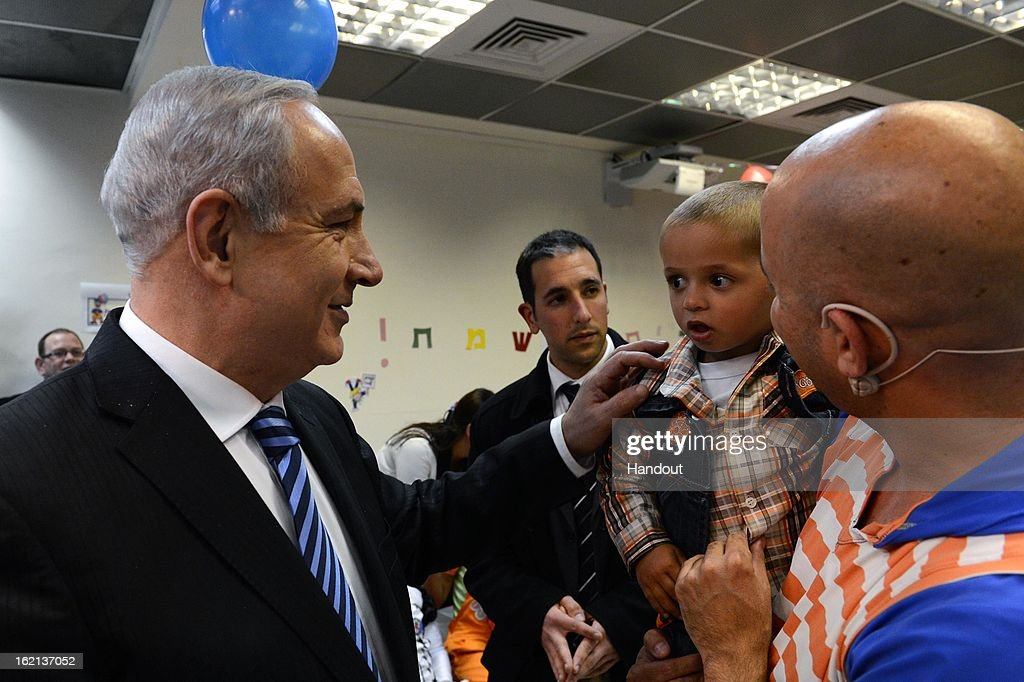 In this handout from the Israeli GPO, Israeli Prime Minister Benjamin Netanyahu greets a child as he hosts child cancer patients of the 'Rachashei Lev' support center ahead of the Jewish holiday of Purim on February 19, 2013 in an unspecified city in Israel. Netanyahu. Rachashei Lev was founded in 1989 to support children and their families suffering and in treatment from cancer.