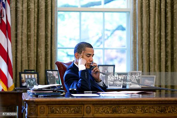 In this handout from the The White House US President Barack Obama sits at his desk in the Oval Office during a phone call with Chinese President Hu...