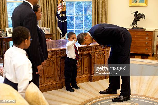 In this handout from the The White House US President Barack Obama bends over so the son of a White House staff member can pat his head during a...
