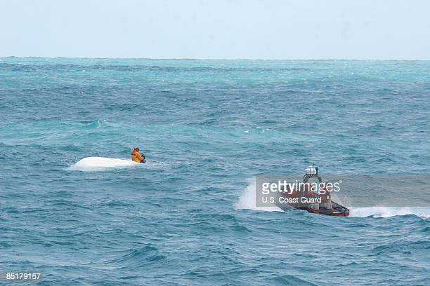 In this handout from the US Coast Guard a Coast Guard boat approaches Nick Schuyler a former University of South Florida football player as he sits...