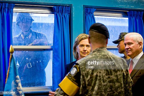 In this handout from the U.S. Department of Defense , a North Korean soldier looks through a window at Secretary of State Hillary Clinton and...