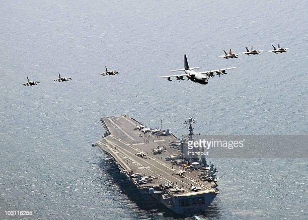 In this handout from the US Navy a US Marine Corps C130 Hercules aircraft leads a formation of F/A18C Hornet strike fighters and A/V8B Harrier jets...