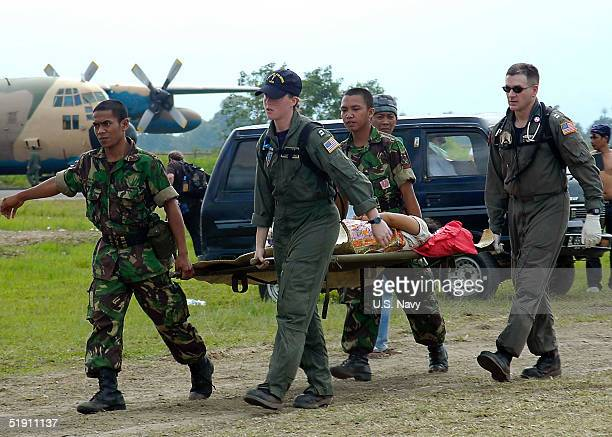 In this handout from the US Navy Lt Lisa Peterson of Derwood Maryland Lt Mark Banks of Savannah Georgia and two Indonesian Army personnel carry a...