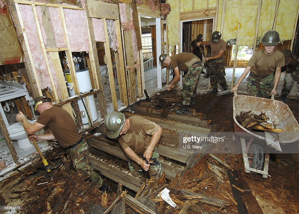 In this handout from the U.S. Navy, S. Navy Seabees, assigned to Naval Mobile Construction Battalion One Three Three, tear through a plywood floor while restoring Hope Haven, a children abuse shelter September 12, 2005 in Biloxi, Mississippi. Bush visited the Gulf Coast for the third time since Hurricane Katrina swept though 15 days ago.