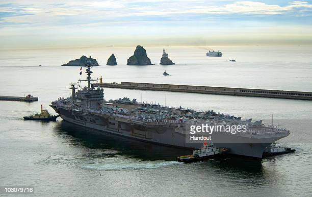 In this handout from the US Navy the aircraft carrier USS George Washington departs on July 25 2010 from Busan South Korea The United States and...