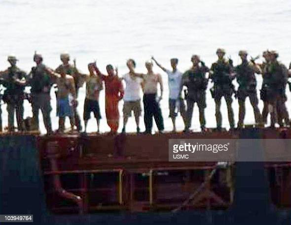 In this handout from the US Navy the US Marine Corps stand on the deck on the M/V Magellan Star with crew members the Marines freed from suspected...