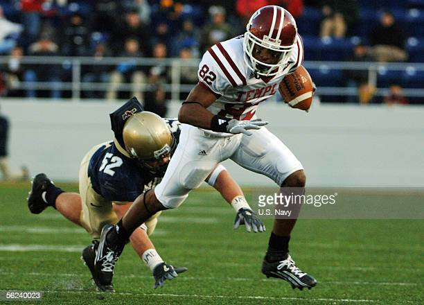 In this handout from the US Navy US Naval Academy linebacker Jake Biles falls short of tackling Temple Owls wide receiver Bruce Francis of the Temple...