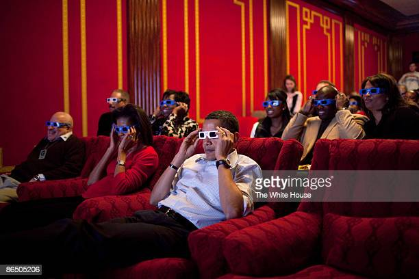 In this handout from the White House US President Barack Obama and first lady Michelle Obama wear 3D glasses while watching Super Bowl during a Super...