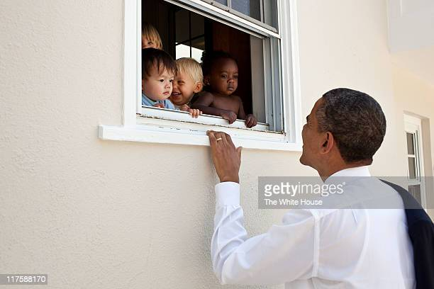 In this handout from the White House US President Barack Obama greets children at a day care facility adjacent to his daughter Sasha's school in June...