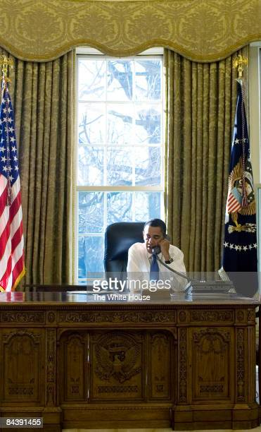 In this handout from the White House, U.S. President Barack Obama talks on the phone in the Oval Office of the White House in the morning January 21,...