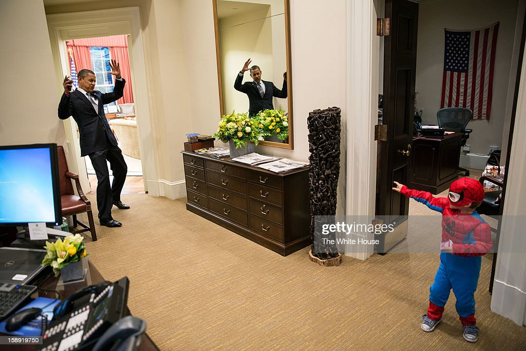 In this handout from the White House, U.S. President Barack Obama pretends to be caught in Spider-Man's web as he greets Nicholas Tamarin, 3, just outside the Oval Office on October 26, 2012 in Washington, D.C. Spider-Man had been trick-or-treating for an early Halloween with his father, White House aide Nate Tamarin in the Eisenhower Executive Office Building.