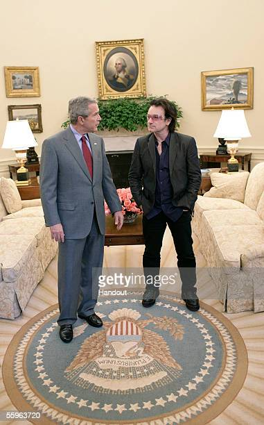 In this handout from the White House US President George W Bush and musician Bono meet in the Oval Office after lunch in the White House October 19...