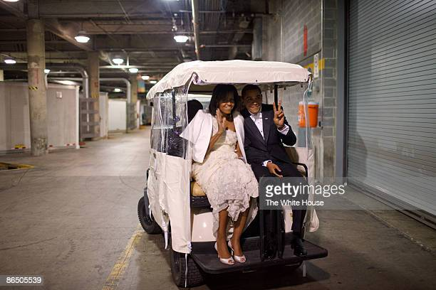 In this handout from the White House US President President Barack Obama and first lady Michelle Obama ride in a golf cart an Inaugural ball January...
