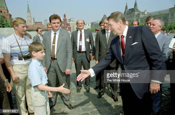 In this handout from the White House US President Ronald Reagan shakes hands with a boy as Mikhail Gorbachev looks on during a tour of Red Square May...