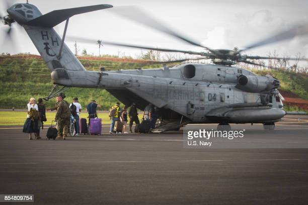 In this handout imade provided by the USNavy US citizens board a US Marine Corps CH53E Super Stallion helicopter assigned to Joint Task Force Leeward...
