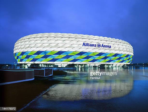 In this handout image from the Allianz Group, the Allianz Arena is illuminated with white, green and blue lights ahead of the UEFA Champions League...