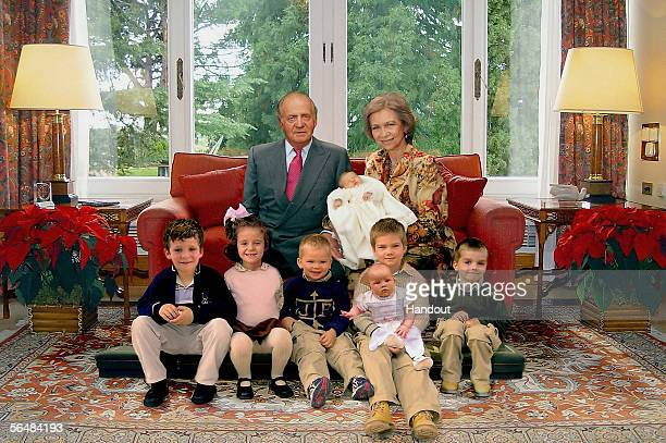 In this handout image from the Spanish Royal House, Spanish King Juan Carlos and Queen Sofia, holding their newborn grandchild Leonor, posing with...