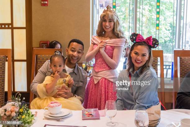 In this handout image John Legend Chrissy Teigen and their daughter Luna pose with Princess Aurora during the Disney Princess Breakfast Adventures at...
