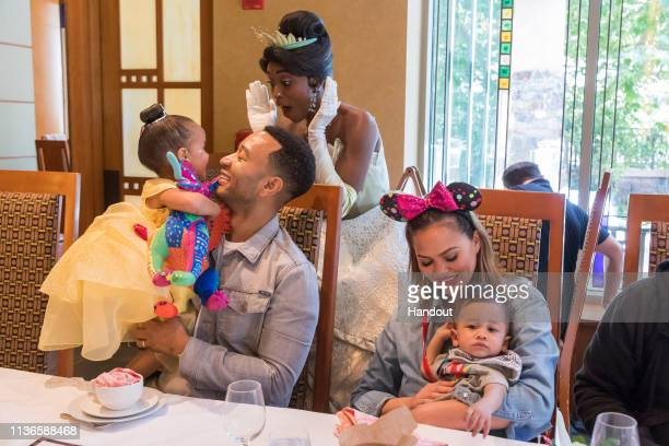 In this handout image John Legend Chrissy Teigen their daughter Luna and son Miles share a moment with Princess Tiana during the Disney Princess...