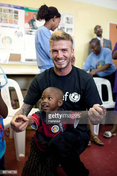In this handout image made available by UNICEF International football star David Beckham in his role as a Unicef ambassador visits a clinic in Cape...