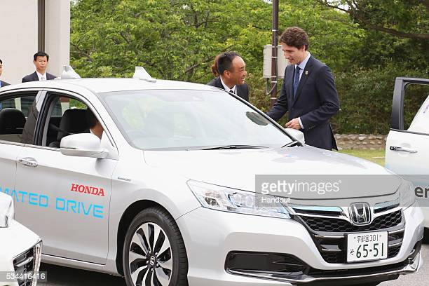 In this handout image provide by Foreign Ministry of Japan Canadian Prime Minister Justin Trudeau rides the automated driving vehicle during the...