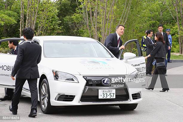 In this handout image provide by Foreign Ministry of Japan Italian Prime Minister Matteo Renzi rides the automated driving vehicle during the...