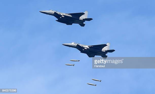 In this handout image provide by South Korean Defense Ministry South Korea's F15K fighter jets drop bombs during a training at the Taebaek Pilsung...