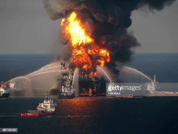 In this handout image provided be the U.S. Coast Guard, fire boat response crews battle the blazing remnants of the off shore oil rig Deepwater...