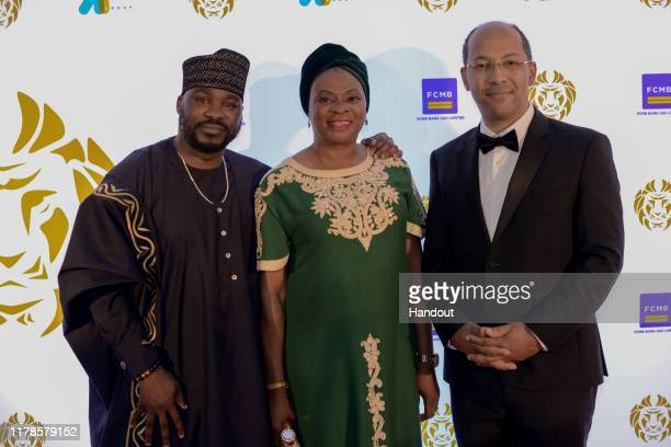 In this handout image provided by APO Group, Alexander Amosu, Founder Lux Afrique, Stella Okuzu and Nicolas Pompigne-Mognard, Chairman APO Group...