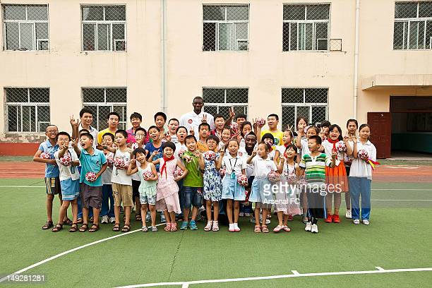 In this handout image provided by Arsenal FC Abou Diaby and Johan Djourou pose with a group of young school children as they visit the Miaopu...