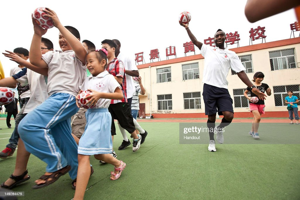 In this handout image provided by Arsenal FC, Johan Djourou plays football with children as he visits the Miaopu Huanghuang School which is funded by Save the Children and Arsenal FC on July 26, 2012 in Beijing, China.